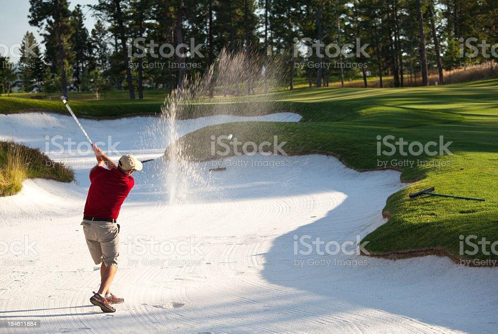 Bunker Blast by Senior Caucasian Golfer stock photo