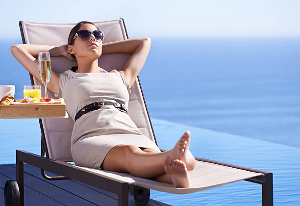 Bunking work for the high life A posh young woman reclining on a deck chair with her hands behind her head high society stock pictures, royalty-free photos & images