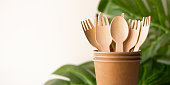 bunner eco friendly disposable kitchenware utensils on white background. wooden forks and spoons in paper cup. and green leaf. ecology, zero waste concept. copyspace.