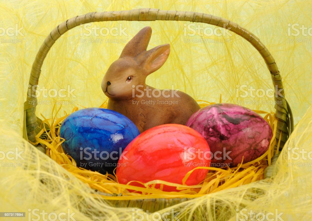 bunny and three painted eggs in Easter nest stock photo