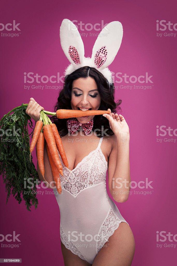 Bunny Girl biting a carrot stock photo