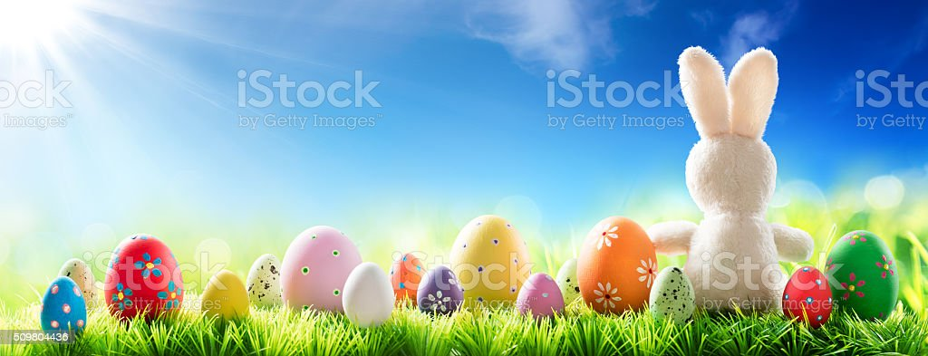 Bunny With Decorated Eggs On Sunny Meadow stock photo