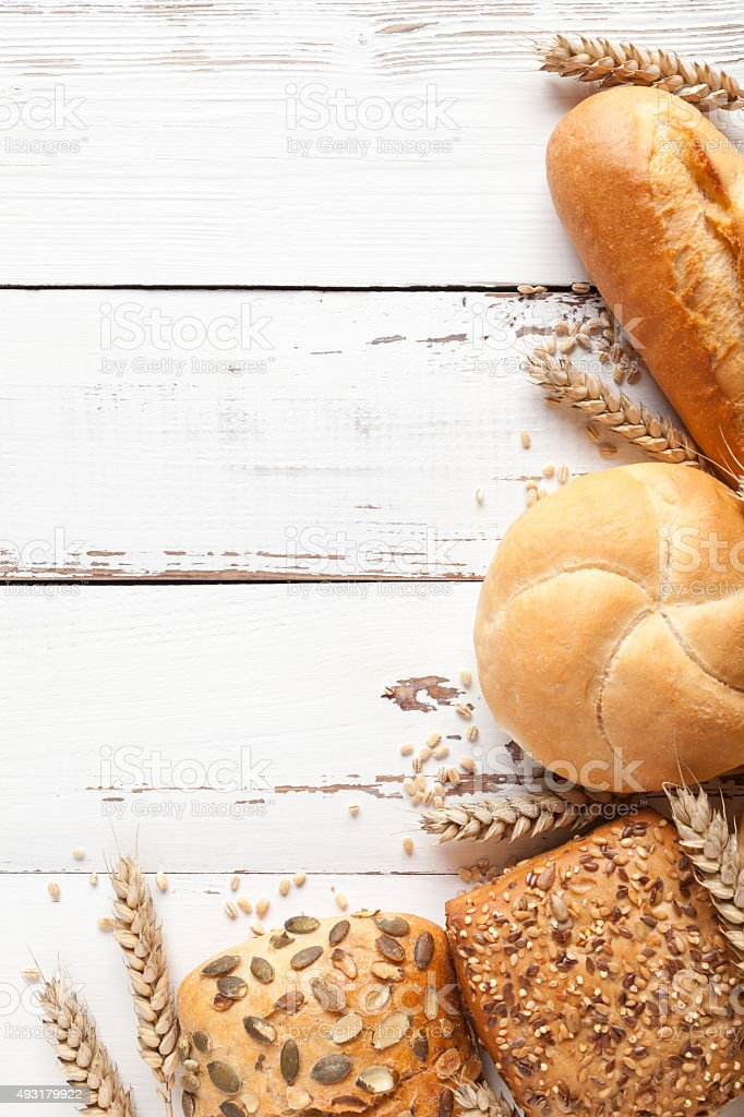 Buns and wheat ears on old white table stock photo