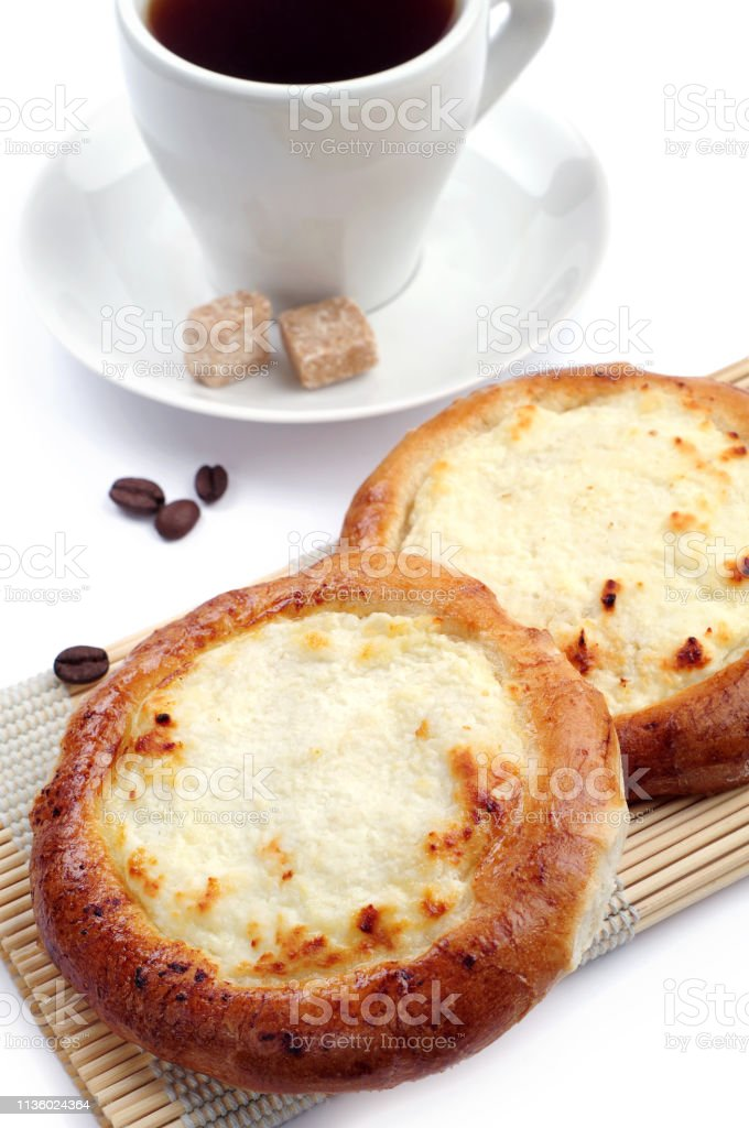 Buns with cottage cheese and coffee cup on white background