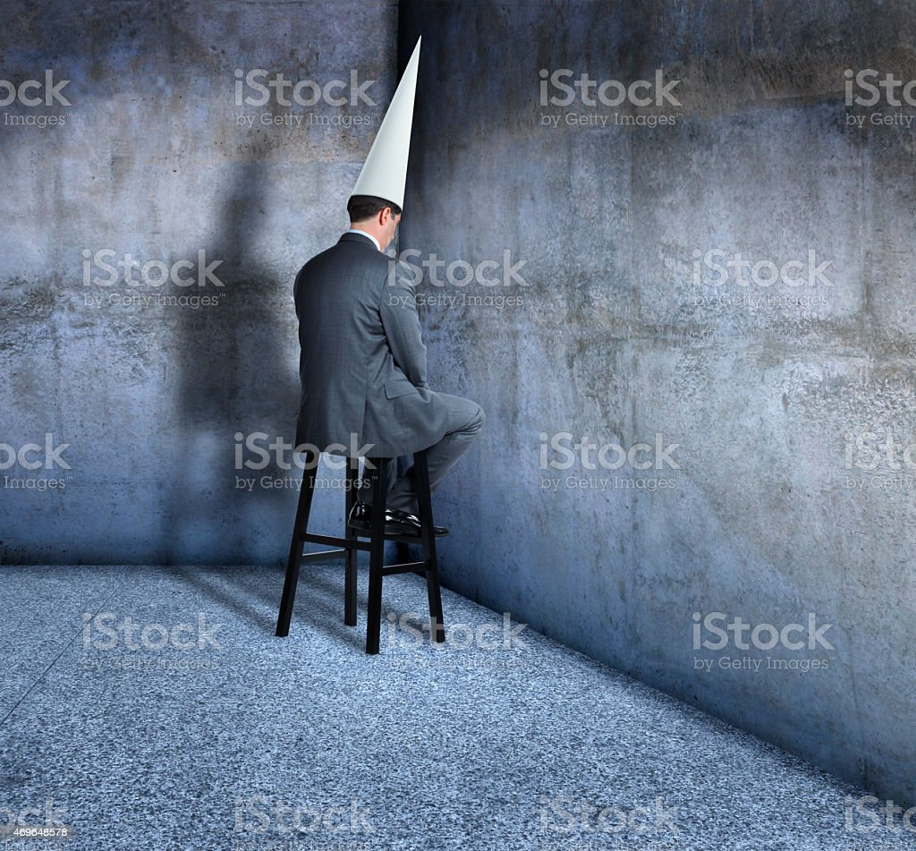 Bunsinessman in dunce cap sits on a stool in corner stock photo