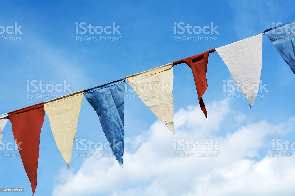 Bunting flags hanging against the blue sky with clouds stock photo
