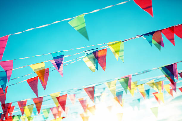 bunting flags on the blue sky background - flag background stock photos and pictures