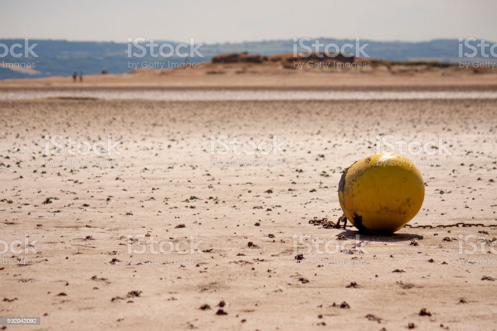 Buoy on a beach at low tide. stock photo