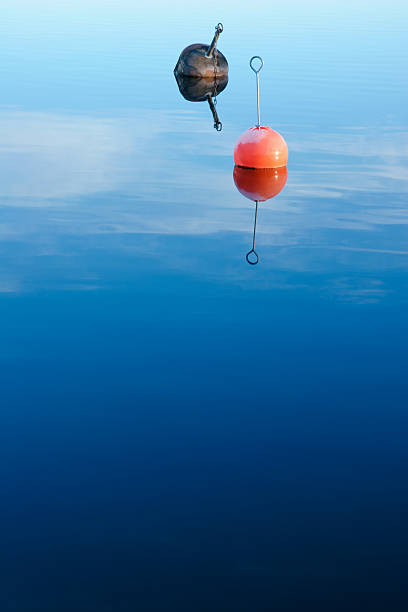 Buoys floating in calm water stock photo