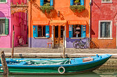 Burano island canal, colorful houses and boats, Italy, Europe