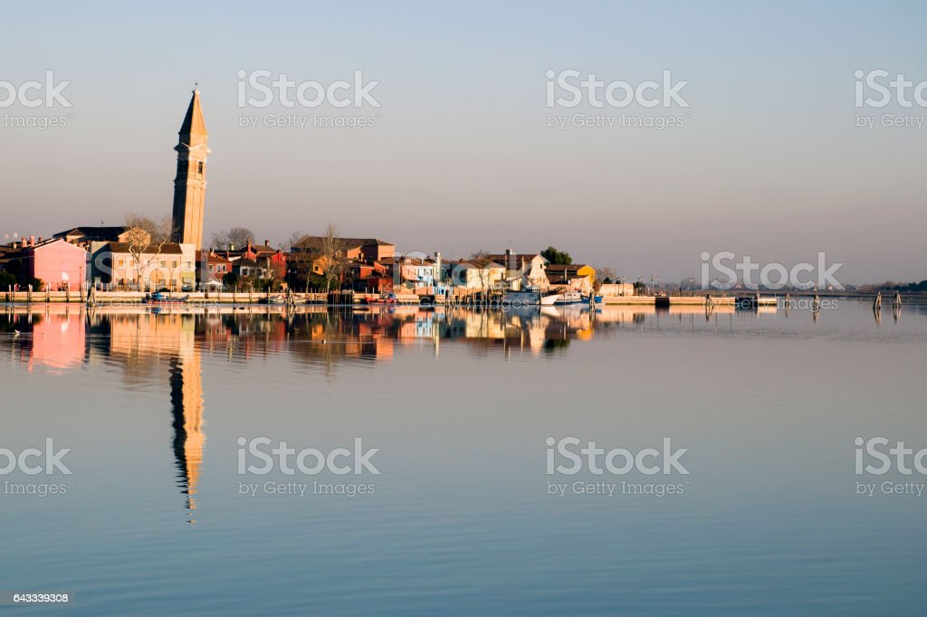 Burano,riflette sull'acqua della laguna le sue case e il campanile che pende stock photo