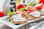 Burato cheese toasts with tomatoes and green salad on a white plate. The concept of healthy eating