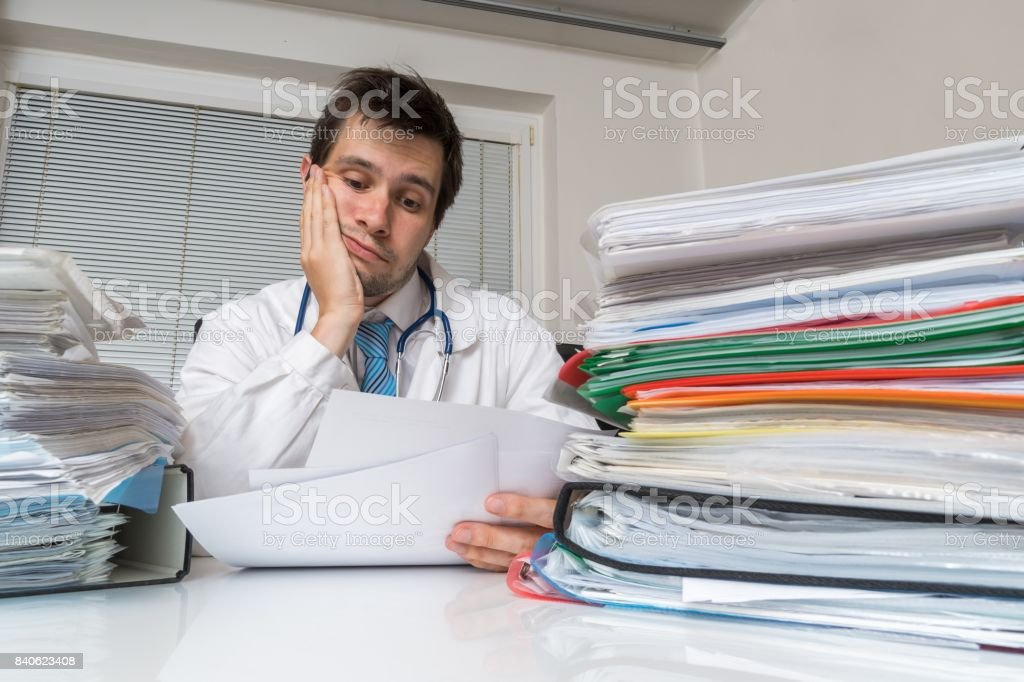 Bureaucracy in medicine concept. Tired overworked doctor is reading medical report. Many documents on desk. stock photo