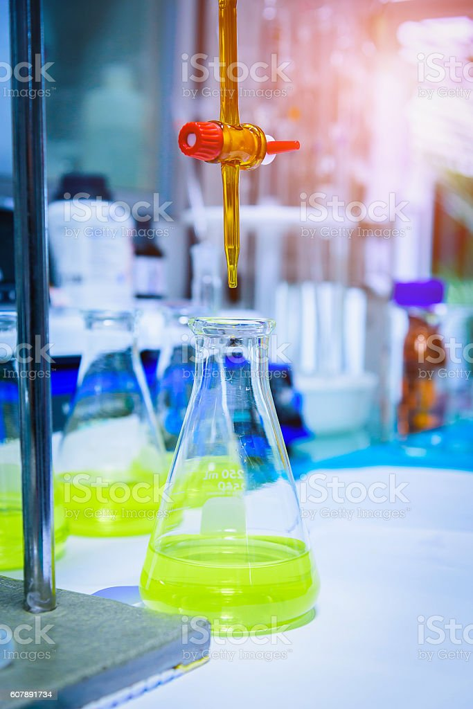 Burette filled with yellow liquid in laboratory. stock photo