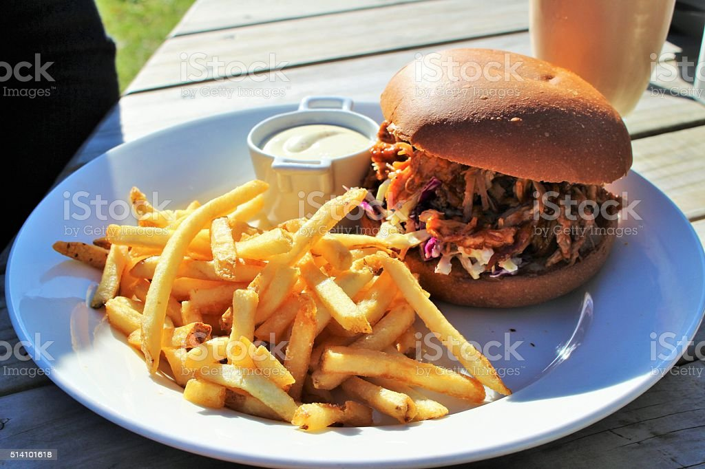 Burger and chips outside in the sun stock photo