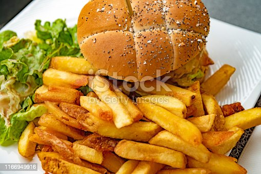 A burger and chips on a plate at a sidewalk cafe in Arcachon, Western France.