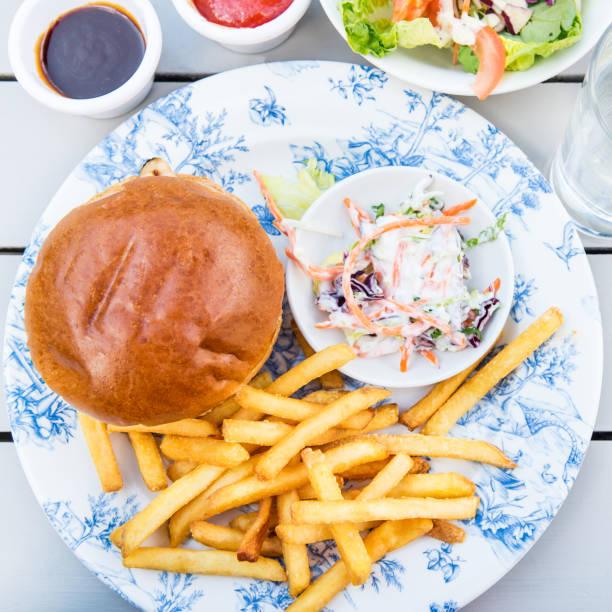 burger und pommes frites mit coleslow salat - englischer erbsen salat stock-fotos und bilder