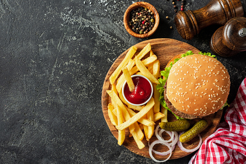 Burger and fries on wooden board on dark stone background