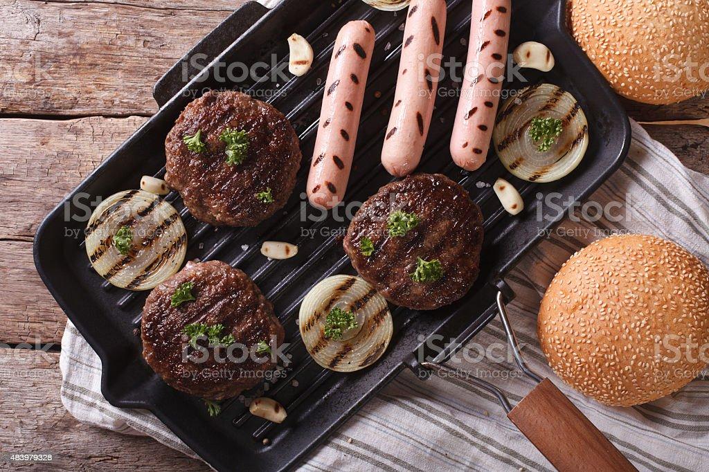 Burger and sausages on grill pan horizontal top view closeup stock photo