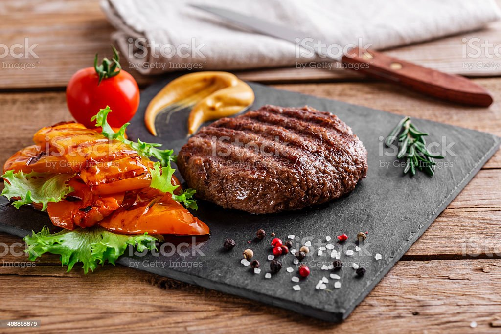 burger grill with vegetables and sauce on a wooden surface stock photo