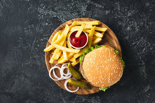 istock Burger, hamburger or cheeseburger served with french fries, pickles and onion 973095652