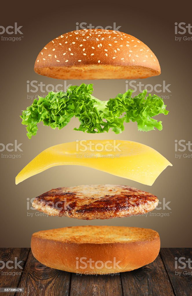 Burger ingridients separated flying in air stock photo