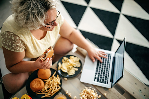 Overweight woman eating fast food in living room