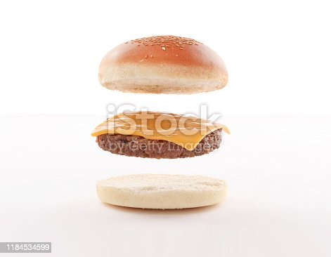 float,fly burger layers with steaks and cheddar on white background