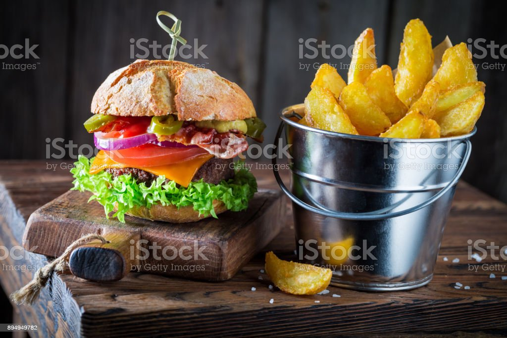 Burger made of vegetables, beef and pepperoni served with chipis stock photo