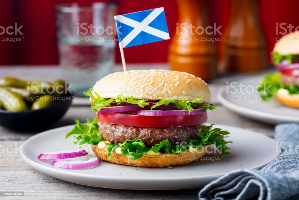 Burger on a plate with pickles. Wooden background. stock photo