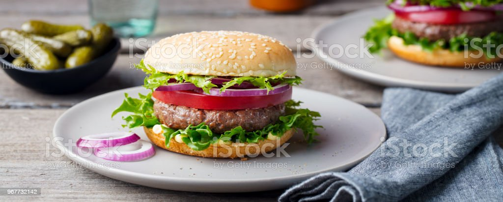 Burger on a plate. Wooden background. Copy space. stock photo