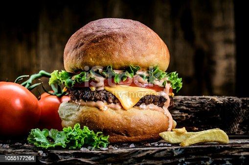 Fresh tasty burger on wooden table