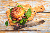 Burger with beef and bacon on wooden table. Top view