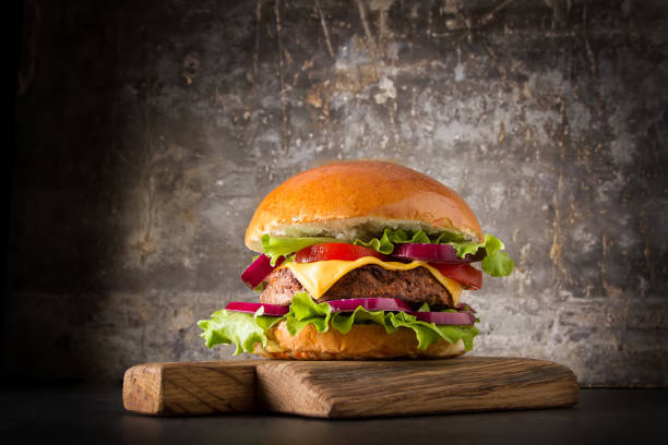 Burger with beef, cheese and tomatoes, American fast food. Gray background. stock photo
