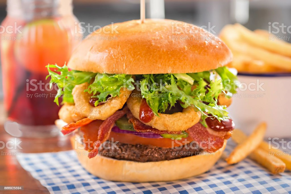 Burger with beef, tomato, onion, pickles, bacon, onion rings, lettuce and barbecue sauce stock photo