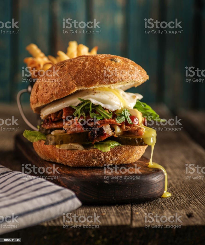 Burger with chopped meat, egg and arugula on a wooden table стоковое фото