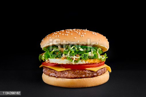 perfect burger with cutlet, cheese, tomato, lettuce, omlette, isolated at black background Copy space