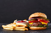 burger with french fries on dark table