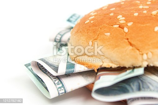burger with hundred dollar bills instead of toppings on a white background isolate, close up