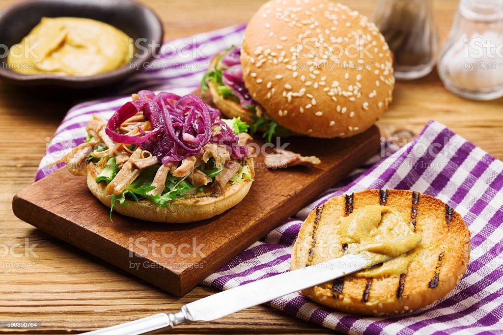 Burger mit Fleisch von Ente mit roten Zwiebeln und Salat. Lizenzfreies stock-foto