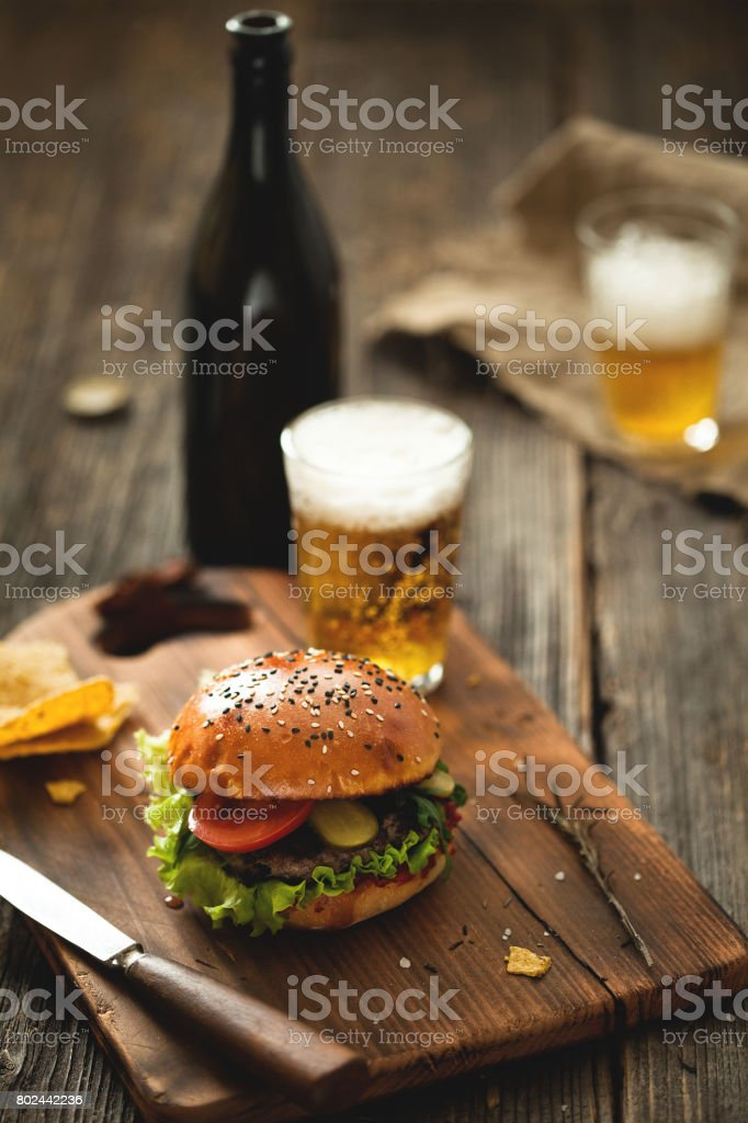Burger with salad and glass of beer on wooden table. stock photo