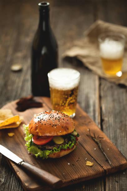 burger mit salat und ein glas bier auf holztisch. - bier gesund stock-fotos und bilder