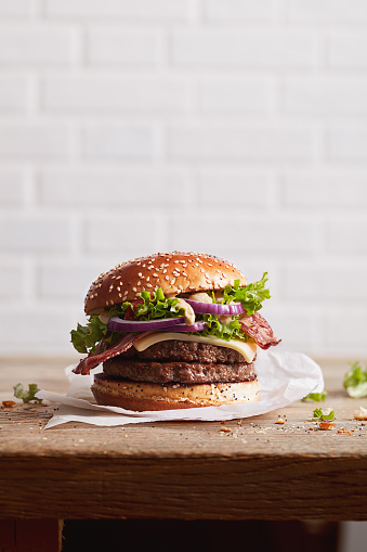 burger with sesame bun with onion rings and juicy fried meat on a white brick wall background