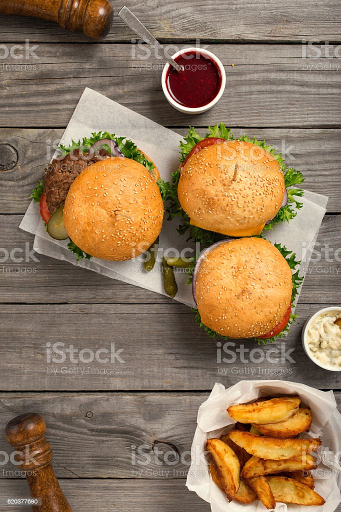 Burgers and rusburger on wooden table with sauces and fries zbiór zdjęć royalty-free