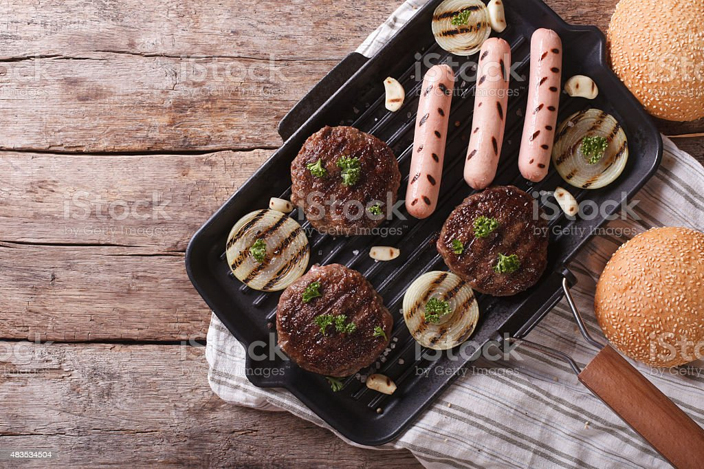 Burgers and sausages on a grill pan horizontal top view stock photo