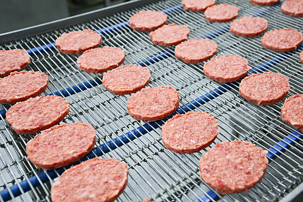 Burgers on Conveyor Burgers are on conveyor just before freezing. . +4 degrees celcius cold room. food warehouse stock pictures, royalty-free photos & images