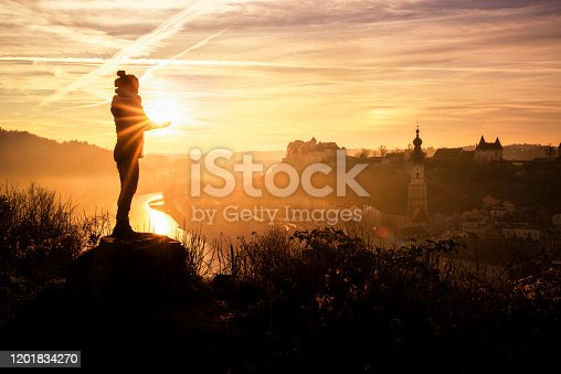Burghausen, Bavaria, Germany. A woman holds the evening sun in her hands. The skyline of the old town is in the background.