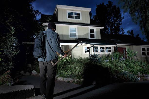 Burglar approaching a home at night stock photo
