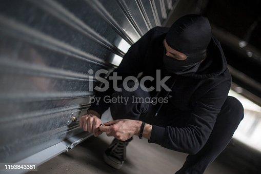 Burglar trying to rob a garage. Unrecognizable Caucasian male wearing a balaclava.