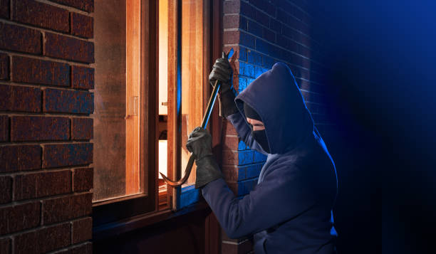 Burglar breaking into a home Hooded masked burglar forcing open a window in a home. thief stock pictures, royalty-free photos & images